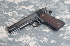 Colt 1911 handgun on camouflage uniform Royalty Free Stock Images