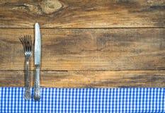 Coltelleria con la tovaglia blu e bianca su legno rustico con lo spazio della copia per la carta del menu fotografia stock