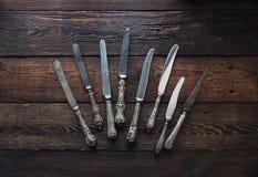 Coltelleria d'annata della cucina - coltelli su fondo di legno rustico Immagine Stock
