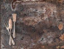 Coltelleria d'argento d'annata sul fondo strutturato rustico del metallo Fotografia Stock Libera da Diritti