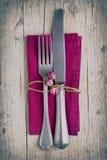Coltelleria - forcella e coltello sul tovagliolo porpora in scaletta d'annata immagini stock