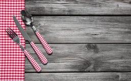 Coltelleria: Il coltello, il cucchiaio e la forchetta su rosso di legno hanno controllato il fondo Fotografie Stock Libere da Diritti