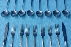 Coltelli, cucchiai e forchette su una tavola blu Fotografia Stock