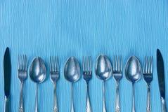 Coltelli, cucchiai e forchette su una tavola blu Immagini Stock Libere da Diritti