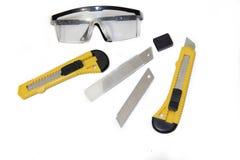 Coltelli della costruzione sugli strumenti bianchi di un fondo su un fondo bianco Oggetti per la riparazione e la raccolta di mob fotografia stock
