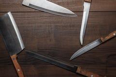 Coltelli di cucina sul fondo di legno marrone della tabella Fotografia Stock Libera da Diritti