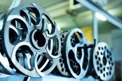 Coltelli per la taglierina o la smerigliatrice sui precedenti dell'impianto di macellazione Immagine Stock