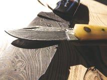 Coltelli taglienti dell'acciaio di Damasco su fondo di legno immagine stock