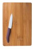 Coltello ceramico con una penna porpora sul tagliere Fotografia Stock Libera da Diritti