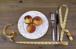 Coltello con una forcella, un piatto, una misura di nastro e le pesche su una b di legno Immagini Stock Libere da Diritti