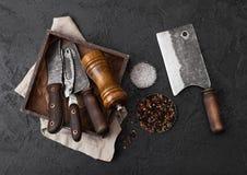 Coltello d'annata della carne e forcella e scure in vecchia scatola di legno sul fondo nero della tavola Utensili del macellaio S fotografie stock