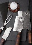 Coltello d'annata della carne e forcella e scuri con il tagliere di pietra ed il fondo nero della tavola Utensili del macellaio F fotografia stock libera da diritti