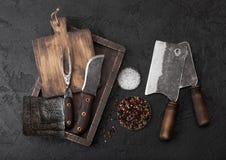Coltello d'annata della carne e forcella e scuri con il tagliere d'annata ed il fondo nero della tavola Utensili del macellaio Fi fotografia stock libera da diritti