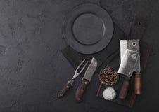 Coltello d'annata della carne e forcella e scuri con il tagliere d'annata ed il piatto sul fondo nero della tavola Utensili del m immagini stock