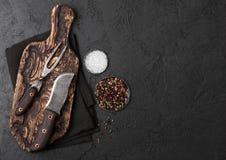 Coltello d'annata e forcella della carne sul tagliere d'annata e sul fondo di pietra nero della tavola Utensili del macellaio Sal immagini stock libere da diritti