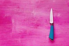 Coltello da cucina su fondo di legno rosa Disposizione piana Fotografia Stock