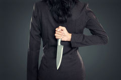 Coltello della tenuta della donna di affari dietro il suo indietro immagini stock