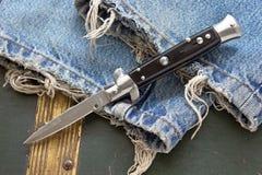 Coltello di coltello a serramanico sui jeans Fotografie Stock Libere da Diritti