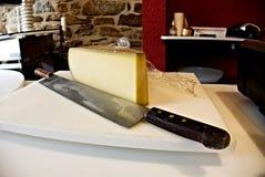 Coltello di taglio del formaggio di Comté fotografie stock libere da diritti