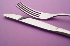 Coltello e dettaglio della forcella sopra un fondo porpora cutlery Immagini Stock