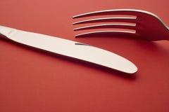 Coltello e dettaglio della forcella sopra un fondo rosso cutlery Fotografie Stock