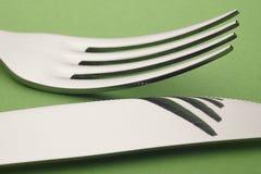 Coltello e dettaglio della forcella sopra un fondo verde cutlery Fotografia Stock Libera da Diritti