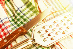 Coltello e grattugia sugli utensili di cucina di una cucina dell'asciugamano tinto Immagini Stock