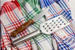 Coltello e grattugia sugli utensili di cucina di una cucina dell'asciugamano tinto Immagine Stock Libera da Diritti