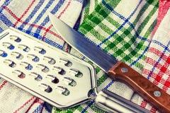 Coltello e grattugia sugli utensili di cucina di una cucina dell'asciugamano tinto Fotografia Stock