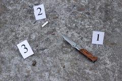 Coltello pieghevole, estremità di sigaretta e manica dalla pistola, sul pavimento, sulla ricerca e sulla prova concreti immagini stock libere da diritti