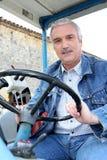 Coltivatore che guida trattore Fotografia Stock