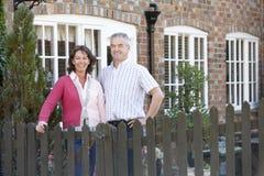 Coltivatore e moglie che si levano in piedi davanti alla fattoria fotografia stock