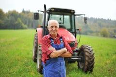 Coltivatore ed il suo trattore rosso Fotografia Stock Libera da Diritti