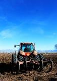 Coltivatore in trattore che ara campo Fotografia Stock