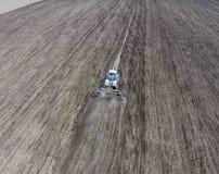 Coltivazione di suolo per la semina dei cereali Il trattore ara il suolo sul campo Fotografia Stock Libera da Diritti