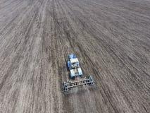 Coltivazione di suolo per la semina dei cereali Il trattore ara il suolo sul campo Fotografia Stock