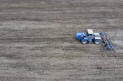 Coltivazione di suolo per la semina dei cereali Il trattore ara il suolo sul campo Immagini Stock Libere da Diritti