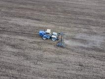 Coltivazione di suolo per la semina dei cereali Il trattore ara il suolo sul campo Immagine Stock Libera da Diritti