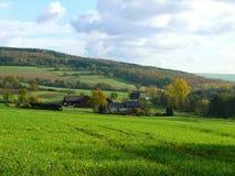 Coltivi alla valle con la crescita di raccolti intorno Fotografia Stock