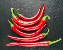 Coltivi i peperoncini rossi freschi, i peperoncini rossi rossi, fondo nero Fotografia Stock Libera da Diritti