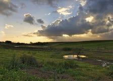 Coltivi il tramonto con le nubi ed i raggi grigi del sole Immagine Stock
