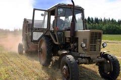 Coltivi il trattore a ruote con la pressa per balle rotonda del fieno sul prato appena falciato Immagine Stock