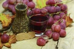 Coltivi la bottiglia di vimini e l'uva del vino organico con l'etichetta Fotografia Stock Libera da Diritti