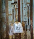 Coltivi la forca dello strumento del ifarm del carretto e due pale contro vecchio uso di legno della parete come la scena rurale d Fotografie Stock