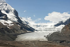 Columbia Glacier dominates the valley. The white glacier capped by blue skies descends in brown dry valley Stock Images