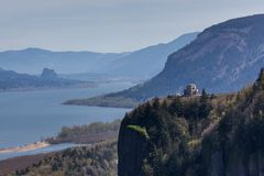 Columbia River Vista House. A view of the Columbia River Gorge with the Vista House on a ledge overlooking the Columbia River and Washington with a hazy sky Stock Photo