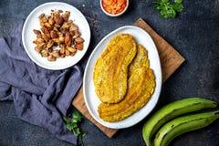 COLUMBIAANS CARAÏBISCH VOEDSEL VAN CENTRAAL-AMERIKA Patacon of toston, gebraden en afgevlakte gehele groene weegbreebanaan op wit stock foto