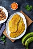 COLUMBIAANS CARAÏBISCH VOEDSEL VAN CENTRAAL-AMERIKA Patacon of toston, gebraden en afgevlakte gehele groene weegbreebanaan op wit stock foto's