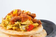 Columbiaanse die arepa met kippenborst en varkensvlees wordt bedekt Stock Foto