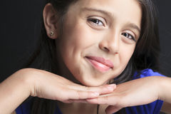 Columbian Little Girl Fun Look in front of a black Stock Image